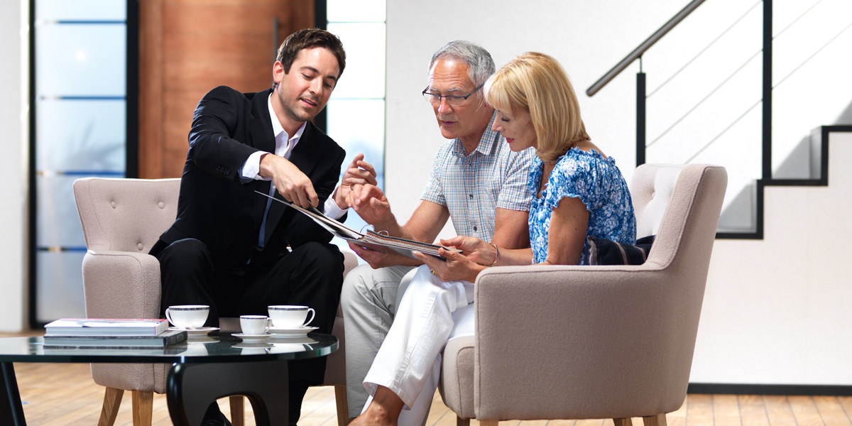 Man consulting elderly couple on home lift options
